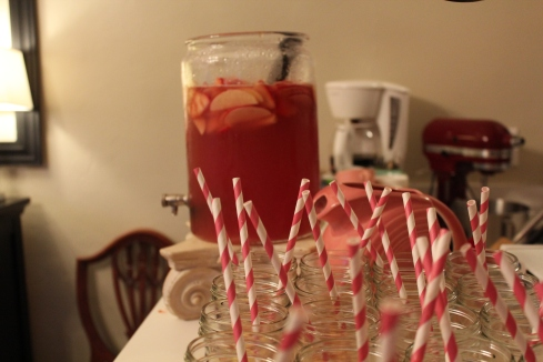 Pink sangria and twirly straws in mason jars.
